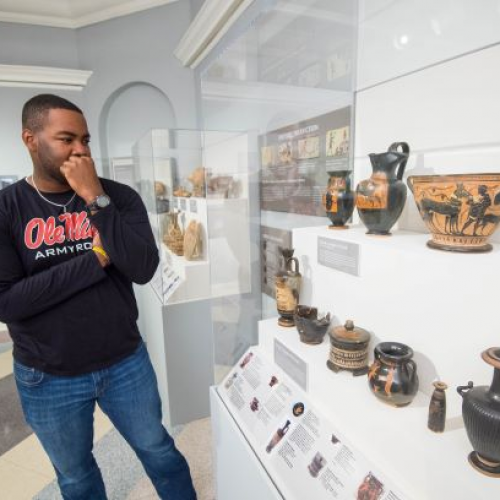 An African American male student is viewing the Robinson Collection of ancient Greek pottery at the UM Museum