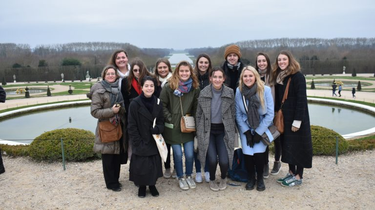 Students on the study abroad trip to Paris gathered together at Versailles