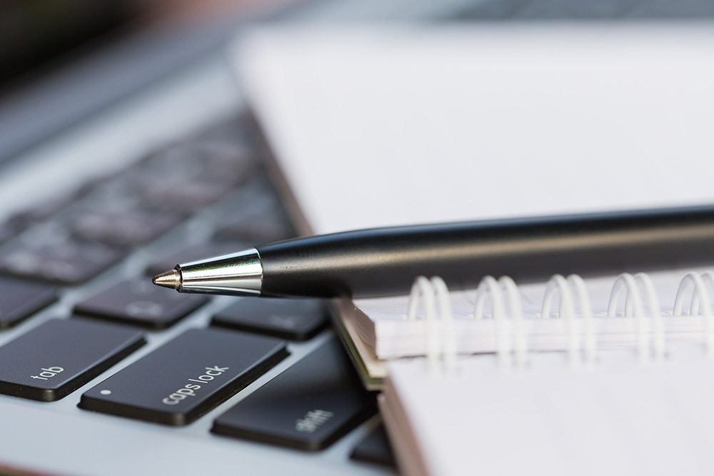 photo of a pen, notebook, and keyboard