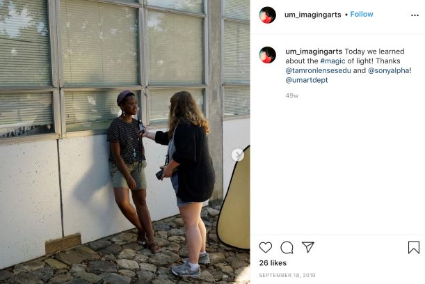 Clicks Instagram post featuring one student posing while the other takes her image. They are learning how to work with light.