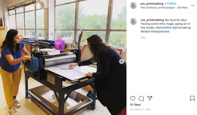 Printmaking Instagram post featuring two students rolling out a print.