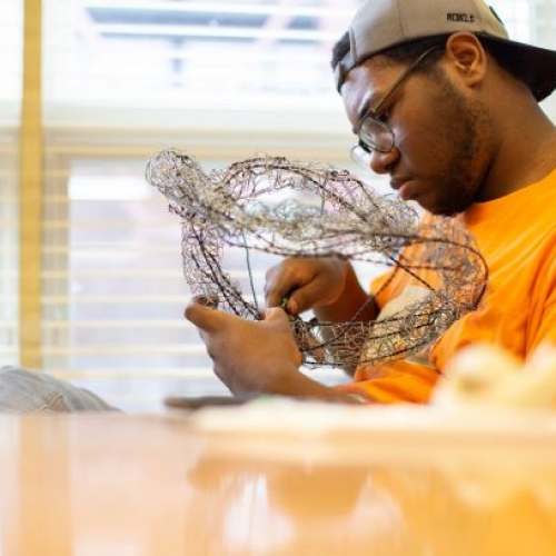 A student is working with wire mesh into a shape for the beginning sculpture course.