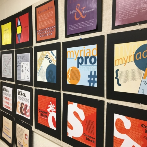 A wall of printed graphics showcasing a variety of typefaces