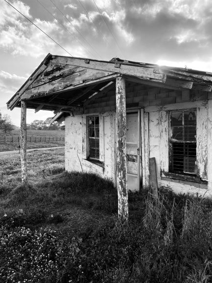 black and white photography of a run-down rural house