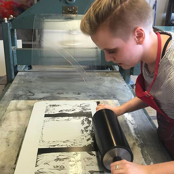 An advanced printmaking student rolls ink onto paper.