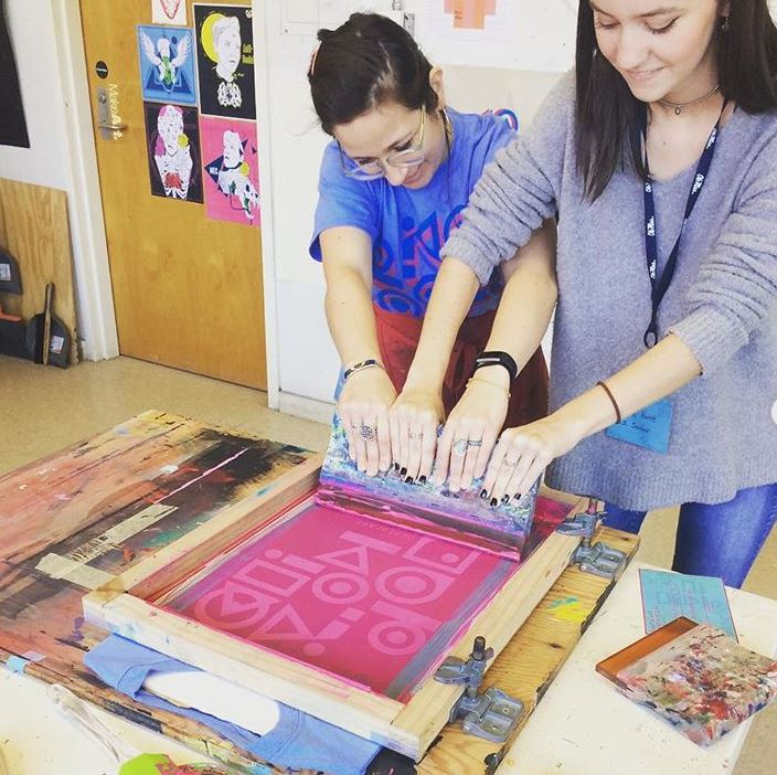 Two women working with the silk screen to create a pink design on a t-shirt