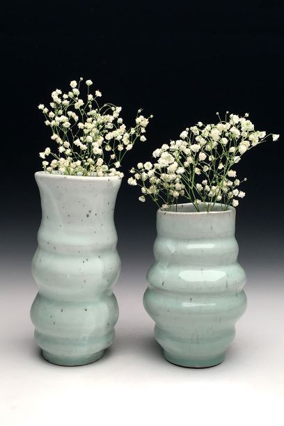 Two light green vases holding white flowers