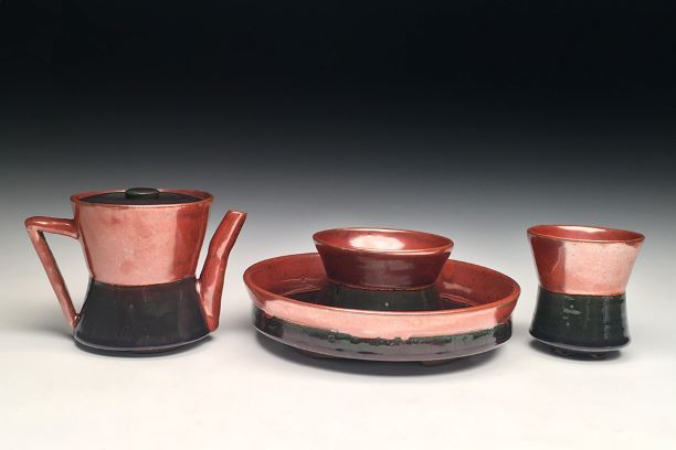 A red, shiny ceramic tea kettle, cups, and a dish