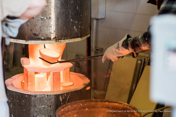 Person removing a glowing hot ceramic bowl from a kiln