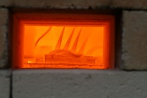a photo looking inside the kiln with glowing red cones