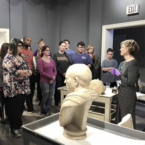 Conservator Amy Jones Abbe gives talk to a class of students at the UM Museum, with the Bust of an Unknown Roman in the foreground.
