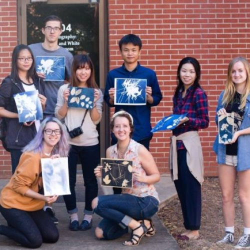 A group of students standing together showing their nature-inspired work after a photography workshop