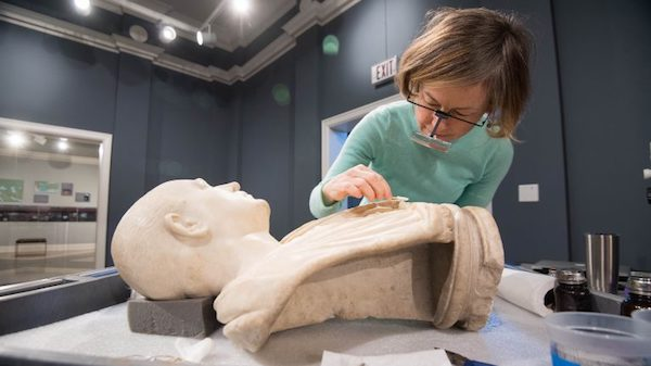 Conservator Amy Jones Abbe gives the Bust of an Unknown Roman a careful cleaning as part of her residency at University Museum.