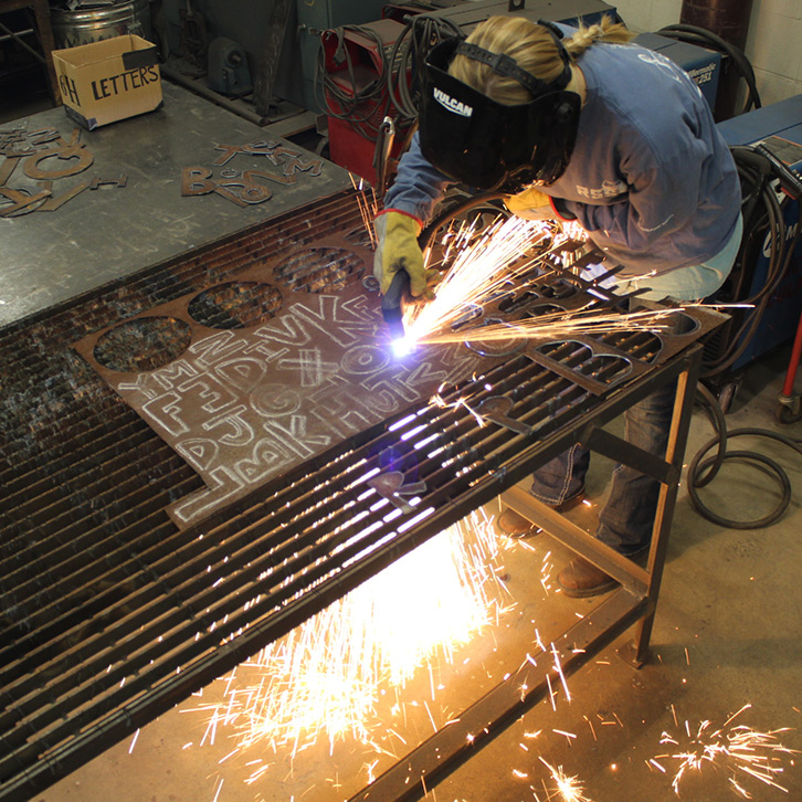 BFA student uses a plasma cutter on a piece of metal for her thesis work.