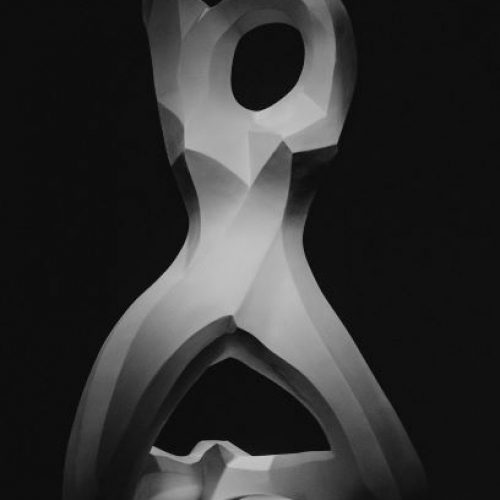 photo of white sculpture against black background. sculpture resembles a human form
