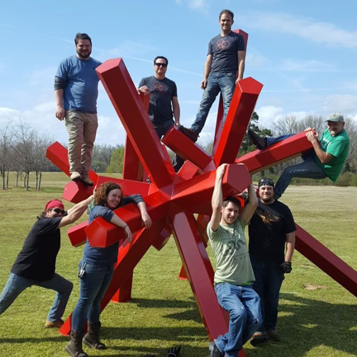 Students, faculty, and a visiting artist Phil Proctor climb on the newest installation of the Yokna Sculpture Trail in Oxford's Lamar Park.