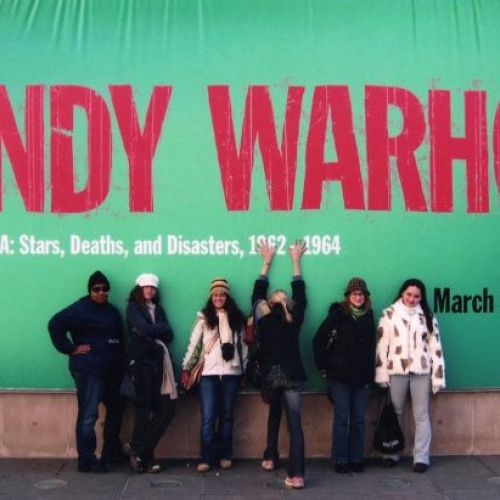 art history students standing in front of a banner for an Andy Warhol exhibit in Chicago.