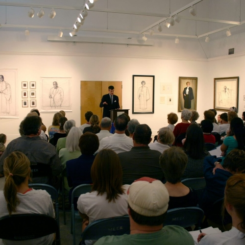 Artist giving a talk to a crowd in the department's gallery.