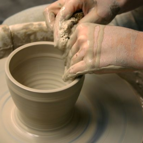 close-up photo of hands creating a bowl on a pottery wheel