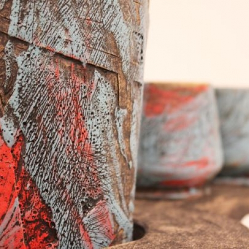 A ceramic piece with rough texture and colors of red, gray, and brown