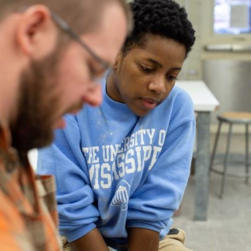 A student observes instructor at the pottery wheel
