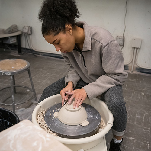 A student spins a ceramic bowl on a pottery wheel
