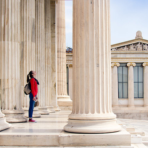 A woman is standing next to large white columns looking up at the architecture