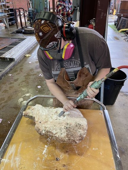 sculpture – MFA student Ashley Smith carving a stone form2