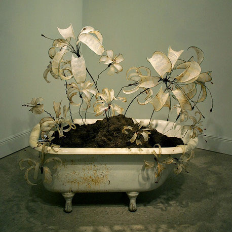 Mixed media sculpture - a bathtub with a large flower growing out of it.